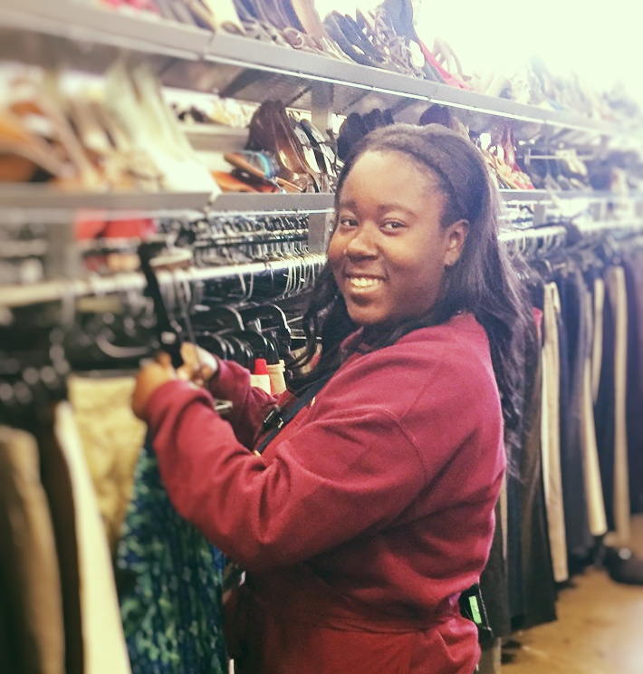 A happy Eco Thrift Store Staff Member arranges clothing